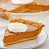 A slice of pumpkin pie with whipped cream on a white plate